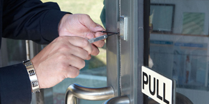 Locksmith picking lock on commercial door